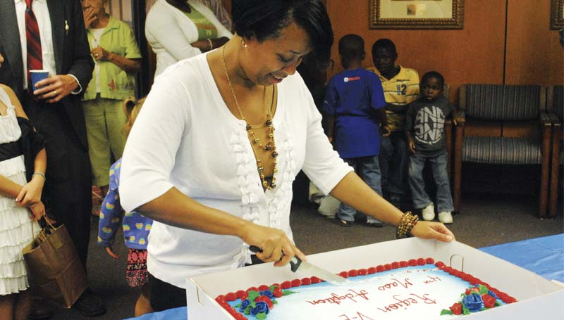 DAILY LEADER / JUSTIN VICORY / Dionna Evans, regional human services director, cuts a cake Friday at the Brookhaven-Lincoln County Government Complex in celebration of the fourth mass adoption in the county since 2010. A total of 12 children ranging in age from three to 14 were adopted by their foster parents Friday.