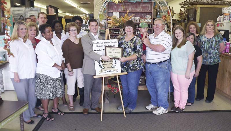 DAILY LEADER / With chamber officials, store employees and well wishers looking on, Brookhaven-Lincoln County Chamber of Commerce Executive Director Garrick Combs presents the Small Business of the Month Award to Rhonda and Billy Joe Deer, owners of Vendors Emporium, on Tuesday.