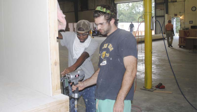 DAILY LEADER / JUSTIN VICORY / Lance Waldrop and Garland Ramsey, both from Brookhaven, frame one of the walls to a modular unit, just one step in a multi-layered assembly line process.