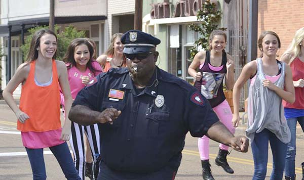 DAILY LEADER / RACHEL EIDE / Sgt. Kenneth Collins, off duty Sunday from the Brookhaven Police Department, and the Showstoppers dancers perform some fancy footwork on Cherokee Street Sunday.
