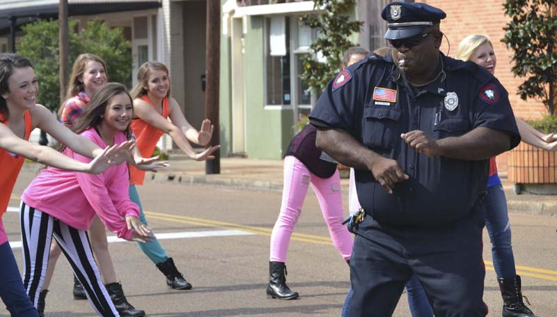 DAILY LEADER / RACHEL EIDE / The Brookhaven Police Department's Sgt. Kenneth Collins uses a few hours of off-duty time to help the Showstoppers Studio Of Dance perform for a video shoot Sunday afternoon under the Homeseekers Paradise sign in downtown Brookhaven. Among the dancers participating are (above from left) Kennedy Moore, 16, who is the daughter of Showstoppers' owner, Holly Moore, and Anna Brooke Richardson, 17. on how to perform the right moves. The video, which will be posted on YouTube once complete, will celebrate the dance studio's 25th anniversary. The videographers planned to shoot additional footage this week at the studio before the final editing and posting online.