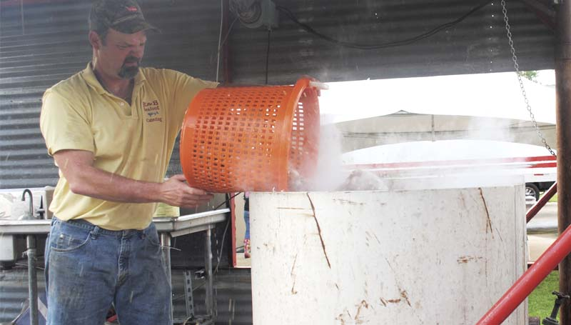 DAILY LEADER / JUSTIN VICORY / In preparation for the Junior Auxiliary's 26th Annual Peel 'Em and Eat 'Em Shrimp Dinner, Kelly Allan of K&B Seafood, dumps a load of shrimp into a giant boiling pot of water Wednesday morning at the Brookhaven Recreation Department. The takeout-only shrimp dinners will be available for pickup Thursday from 3 until 7 p.m. at the rec department on Highway 51 North. JA also will host its annual sweet shoppe with tasty goodies offered for sale. Shrimp dinner tickets at $10 each are still available. Call Valarie Oglesby at (601)757-0551 for information.