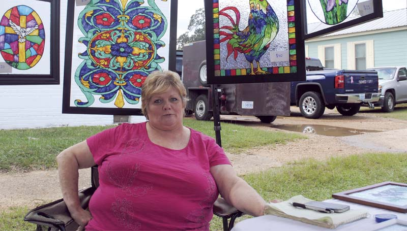 Martha Williamson surrounds herself with handmade stained-glass creations at the Wesson Flea Market Saturday.