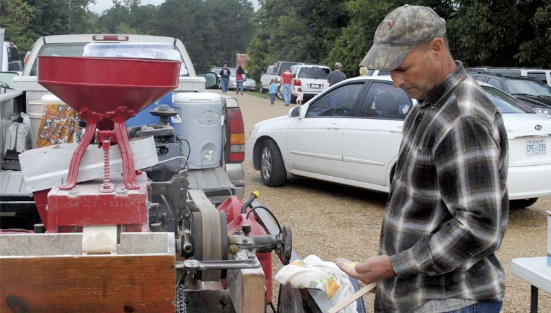 Dewitt Parrett examines freshly ground cornmeal produced onsite by his portable mill at the Wesson Flea Market Saturday. The flea market is staged each year by the Wesson Volunteer Fire Department, drawing crowds of shoppers to the town's downtown area.