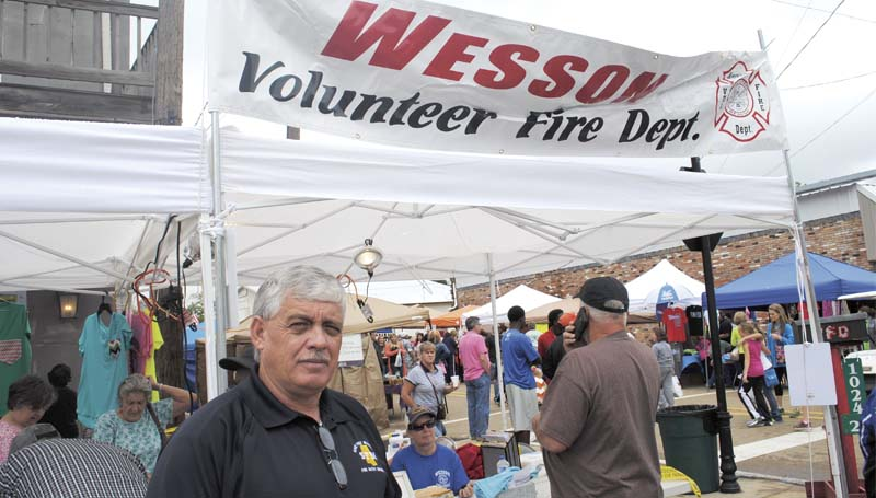 David Clanton, with the state fire marshal's office, teaches kids about fire safety as he stands in front of the Wesson Volunteer Fire Department booth at the flea market Saturday.