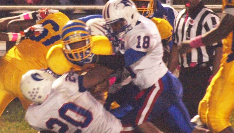 DAILY LEADER / TRACY FISCHER / Wesson defenders Kendrick Brown (20), Davion Frye (18) and Justin Boone (66) teams up to bring Jefferson County runner Rashard Brown (2) Friday night.