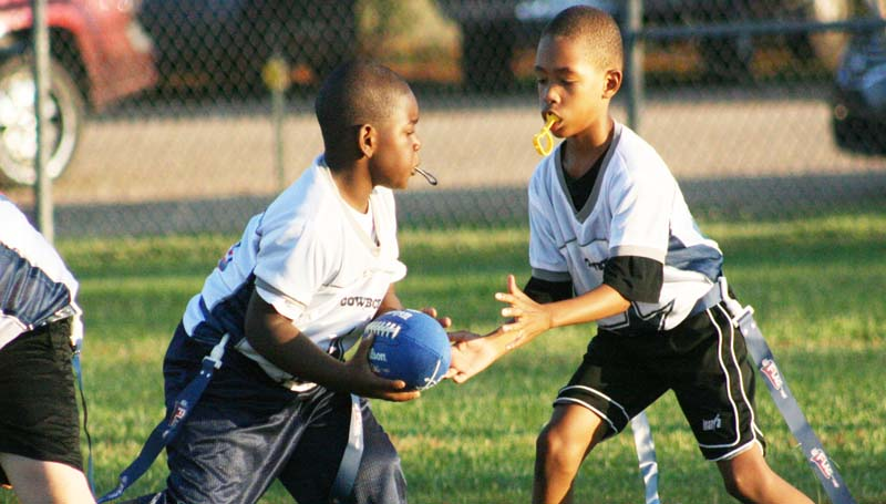 Cowboys quarterback Lajavion Nelson hands off to his teammate, Tyquarius Terrell in Tuesday's  BRD Flag Football action at the Hansel King Sportsplex.