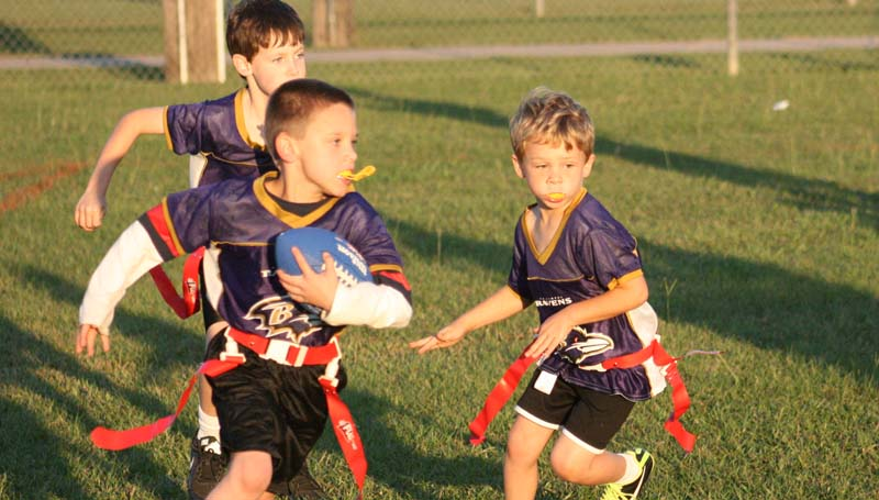 Ravens running back Gavin Hawley (center) looks for some running room as David Williams and Madison Williams prepare to lead the way Tuesday in BRD 5-to-6-year-old flag football action at the Hansel King Sportsplex.