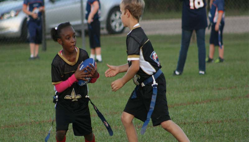 DAILY LEADER / MARTY ALBRIGHT / BRD Saints running back Angel Wilkinson (left) receives a handoff from Manny Miller. The Saints blanked the Bears 36-0 Tuesday to advance to the championship game and play the 49ers Saturday in 7-to-9-year-old flag football action at the Hansel King Sportsplex.