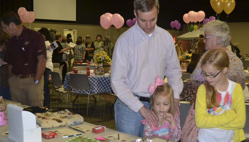 Tim Slay and daughters Abby and Ellie Slay look over the silent auction items Monday night.