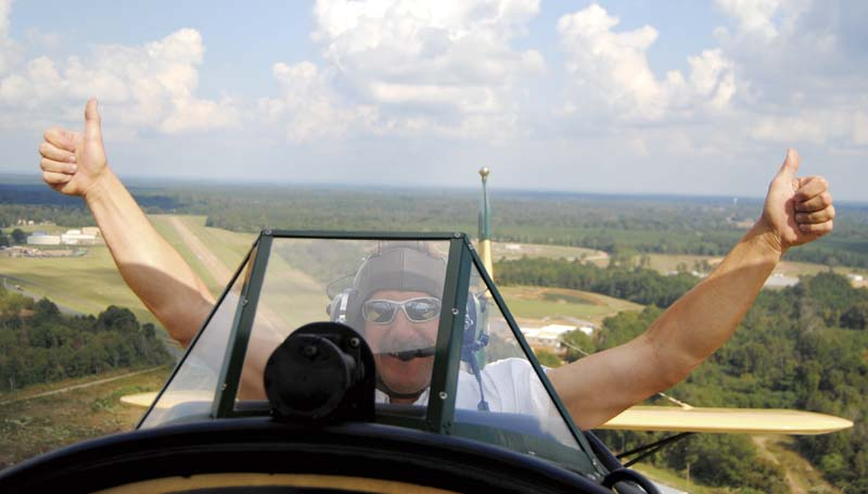 DAILY LEADER / TAMMIE BREWER / Barnstormer Ted Davis gives the two-thumbs up sign (above) during a flight over the Brookhaven area Monday afternoon shortly after takeoff from the Brookhaven Airport. Davis of Brodhead, Wis., brought his 1929 New Standard Biplane (right) to Brookhaven as part of the Biplane Rides of America Dixieland Tour and is offering rides for area would-be barnstormers.