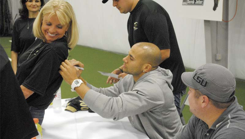 DAILY LEADER / Wide receiver of the New Orleans Saints, Lance Moore, signs the back of Carole Thompson's shirt at the King's Daughters Medical Center autograph signing event Monday night at the KDMC Performance Center.