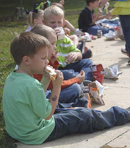 Hayden Sykes, a first-grader at Enterprise Attendance Center, takes a big bite out of his sandwich Tuesday during a picnic at Bicentennial Park.