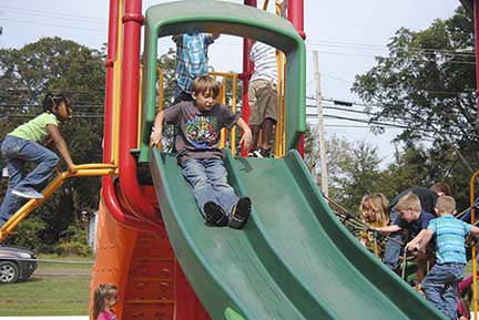 Kolby Sagely, a first-grader at Enterprise Attendance Center, takes his turn down the slide at Bicentennial Park Tuesday morning. After enjoying a picnic meal, the school's kindergarten and first-grade students played before returning to the school.
