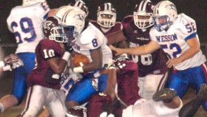 DAILY LEADER / TRACY FISCHER / Wesson running back Nick Lewis (8) tries to overpower Hazlehurst defenders Deangelo McCoy (10) and Raiko Williams (66) for positive yardage Friday night.