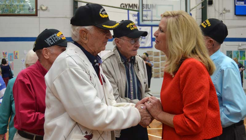 DAILY LEADER / RACHEL EIDE / World War II veteran Clell King (above left) chats with Mississippi State Treasurer Lynn Fitch (right) after the Brookhaven Academy Veterans Day program Monday morning as other local World War II veterans gather around. Fitch was the keynote speaker for the BA event.
