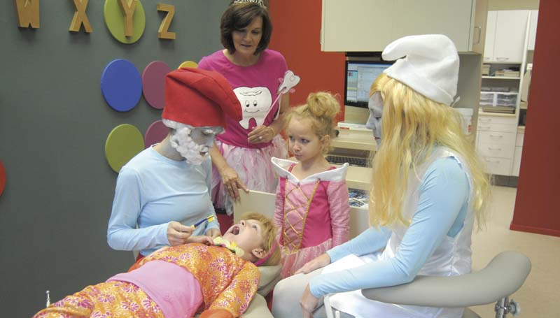 DAILY LEADER / TAMMIE BREWER / Papa Smurf (left), aka Dr. Joey Sessums, teaches Lydia Bass, 7, the proper technique of brushing teeth as her sister Sylvia (standing), 6, listens intently and Papa Smurf's assistant, Smurfette, aka Juli Johnson, (right) and the Tooth Fairy, aka Denise Thames, look on.