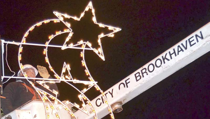DAILY LEADER / RACHEL EIDE / Howard Williams with the city of Brookhaven makes adjustments after installing and turning on one of the Christmas lights on South Railroad Avenue Thursday night.