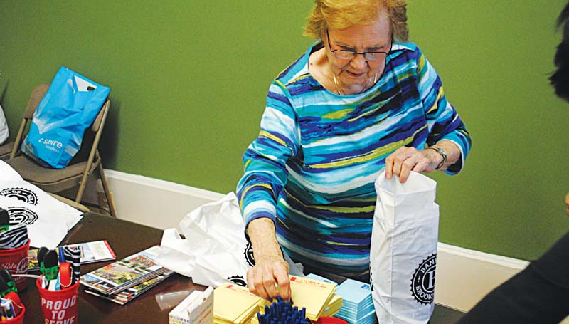 DAILY LEADER / JUSTIN VICORY / Catherine Dickey assembles welcome bags for veterans Friday afternoon at the Brookhaven-Lincoln County Chamber of Commerce. The bags will be presented to veterans at the Lincoln Civic Center program Monday afternoon.