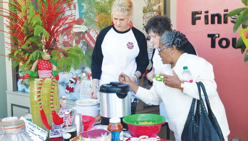 DAILY LEADER / RACHEL EIDE / Helen Griffin (right) asks a question as Kayla Hart (from left) and Joyce Smith, both with The Finishing Touch, describe the items on the store's refreshment table Saturday for the Brookhaven Christmas Open House. Hart is the daughter of storeowner Donna Carollo, and Smith is Carollo's mother.