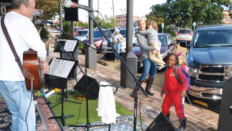 DAILY LEADER / RACHEL EIDE / Johnny Rainer (from left) and his band perform Saturday in front of the Inn on Whitworth downtown while Rainer's daughter, Isabel Smith, takes a break from singing to hold her son, Prentiss Smith, 4, while Prentiss's sister Eliza Smith, 4, (in back ground) and Kliziana Watson, 5, tap their feet to the music. The Inn was among nearly three-dozen businesses participating in the Christmas Open House Saturday.