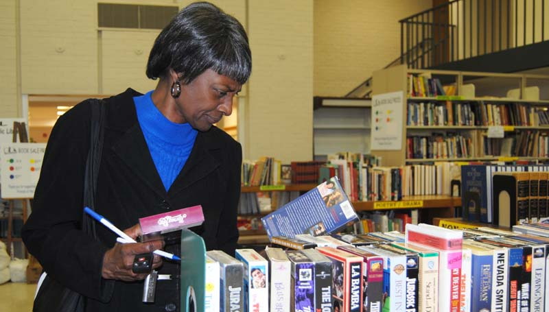 DAILY LEADER / TAMMIE BREWER  / Brenda Perkins of Brookhaven looks through a collection of movies that are available for purchase at the Friends of the Lincoln County Public Library Holiday Book Sale last week. Perkins said she loves old movies. Friends' volunteer Eric Kaplan said as of last week, more than $1,500 had been raised so far for the fundraiser, which will run through Saturday, Nov. 16.