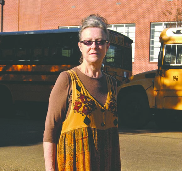 Bea Teasley stands in front of buses waiting for school to let out at Brookhaven Elementary. She was a student at that school in 1963 and remembers the anxious ride home on the bus after Kennedy was slain.