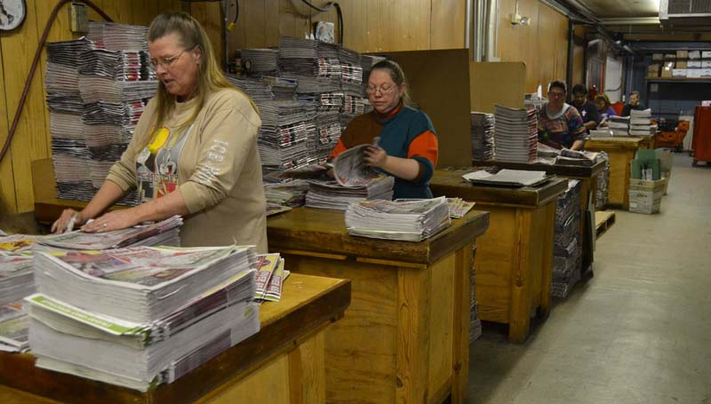 THE DAILY LEADER / RACHEL EIDE / The Daily Leader mailroom staff members, including (from left) Mary Temple, Lee Marbury and others, work to assemble today's big holiday edition of the newspaper, which is being delivered to all local residents as The Daily Leader's gift to the community. Some 19,000 copies of the newspaper will be distributed today.