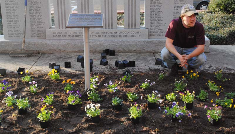 THE DAILY LEADER / JUSTIN VICORY / Gage Gatlin takes a short break after planting flowers in front of the Brookhaven-Lincoln County Government Complex Tuesday afternoon.