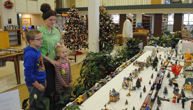 """THE DAILY LEADER / RHONDA DUNAWAY / Ten-year-old John Paul Farr (left), of Brookhaven, and his little sister, Carly Farr, 6, examine details of Maxine Allen's Christmas Village with library intern Alexis Smith, 22, of Brookhaven, in the lobby of the Lincoln County Public Library Wednesday afternoon. Allen has been setting up her snow village in the library lobby each Christmas season for the last several years. """"I started collecting 18 years ago when co-worker, Carolyn Douglas, gifted me with a church and a library,"""" Allen said. """"Family, friends and co-workers have been finding pieces to go in my set since then. Currently, I am looking for a pharmacy and a hospital to complete the village."""""""
