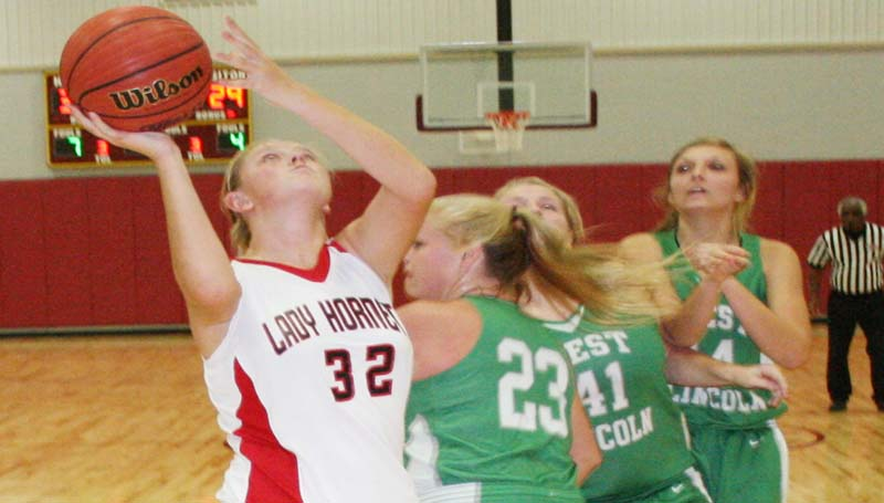 DAILY LEADER / MARTY ALBRIGHT / Loyd Star's Hannah Dickerson (32) scores an easy basketball as West Lincoln's defenders hustle in to deny the shot Thursday afternoon.