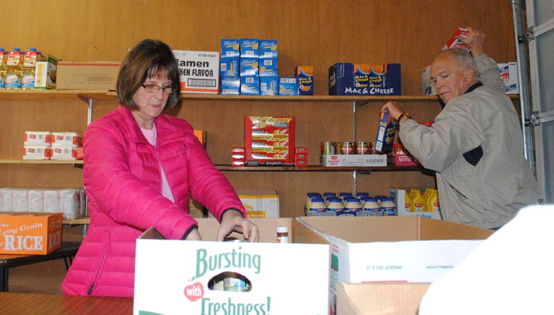 THE DAILY LEADER / JUSTIN VICORY / St. Francis of Assisi/St. Vincent De Paul pantry director Paula Gennaro and Mark Nettles stock food into individually portioned boxes at the church's food pantry Thursday afternoon.