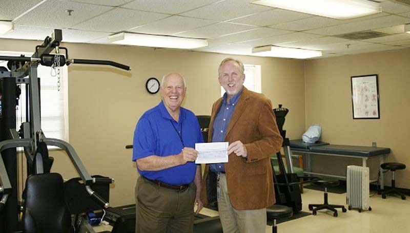 PHOTO SUBMITTED / Georgia-Pacific Monticello recently presented a check for $7,000 to Lawrence County Hospital administrator Semmes Ross (left). Presenting the check in the hospital's physical therapy room is Ray Melick, public affairs manager for Georgia-Pacific's Monticello mill.