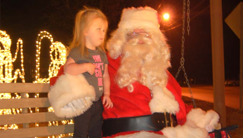 Emory Porter (standing), 2, takes a good look at Santa Claus (Darvin Bardwell) during her visit Thursday night at the intersection of North Jackson Street and Industrial Park Road. Santa and his helpers will be passing out candy at the intersection each night from 6 until 8 p.m. until Monday.