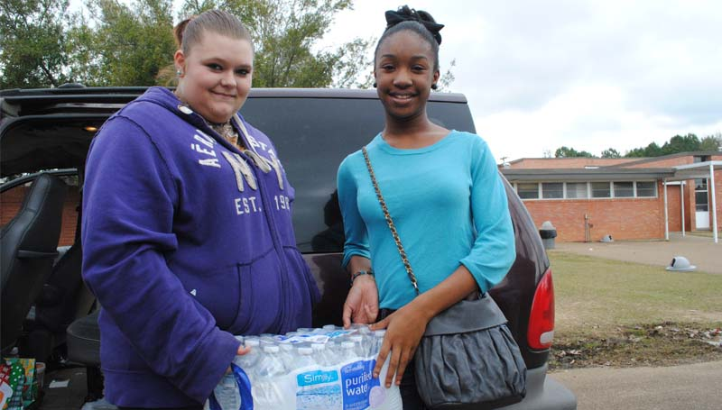 THE DAILY LEADER / JUSTIN VICORY / Alexander junior high students Brittany Bessonette (left) and Jalen Hardy spearheaded a charitable donation drive for children in the Philippines. After raising money to purchase 27 cases of water, the two traveled to the Salvation Army in McComb last week to ship them more than 13,000 miles away.