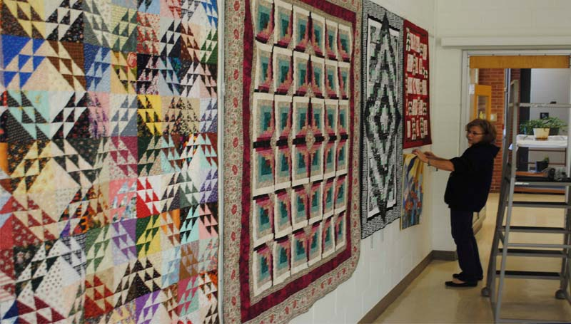 THE DAILY LEADER / JUSTIN VICORY / Connie Anderson helps arrange quilts Friday for the public to take in at the Lincoln County Public Library. Anderson's own quilts are among those displayed at the library this month.
