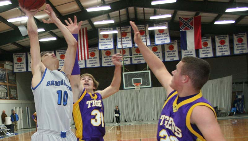 DAILY LEADER / MARTY ALBRIGHT / Brookhaven Academy's Todd Gagliano (10) scores an easy basket for the Cougars as Centreville's defenders Kole Chandler (23) and Austin Addington (31) stretches to block the shot Monday night in John R. Gray Gymnasium.