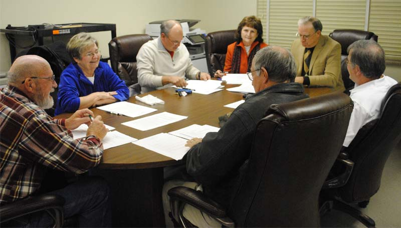 THE DAILY LEADER / RHONDA DUNAWAY / Lincoln County School Board members Jack Case (from left), Kay Coon, Ricky Welch, administrator Regina East and Superintendent Terry Brister look over and sign papers at the Monday meeting.
