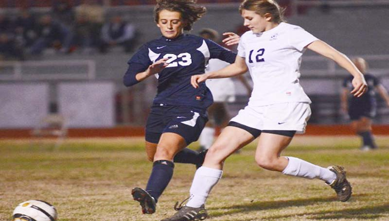 DAILY LEADER / SCOTT BOYD / Brookhaven High's Katie Grace Culpepper (12) battles with Pearl's Kelli Green in Tuesday night's soccer game in Brookhaven. The Lady Panthers (5-7-2) lost to Pearl 4-0. In the boys' game, the Pirates defeated the Panthers (2-10-2) 9-0. With the loss, Brookhaven still clinched second place in district action and made the playoffs that starts Jan. 28.