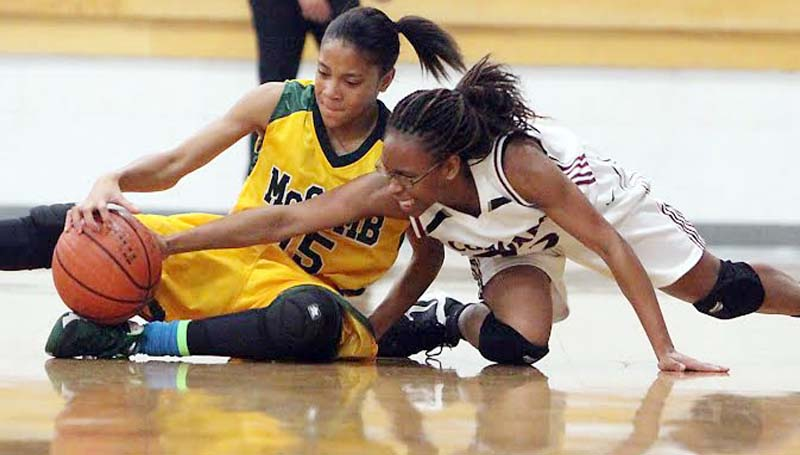 DAILY LEADER / JONATHON ALFORD / Lawrence County's Latasha Rhodes and McComb's Chardonay Williams (15) battle for the loose ball Friday night in Monticello.