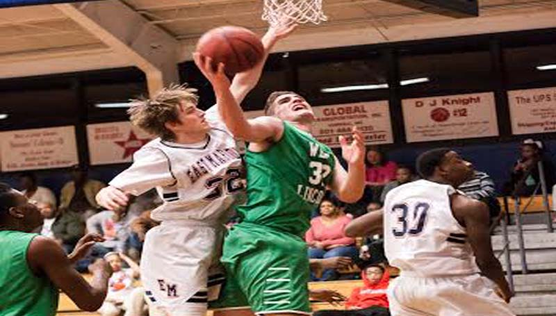 DAILY LEADER / TERESA ALLRED / West Lincoln's Sam Bivens shoots a tough shot under the basket as East Marion's defender Tre Tolar (32) tries to block the attempt Friday night.