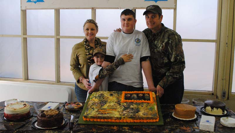 THE DAILY LEADER / RHONDA DUNAWAY / The Vidrine family, Cricket (from left), Cole, Keegan and Scott, of Lafayette, La., are honored Saturday at Georgia-Pacific's Monticello Mill pavilion with a special cake at a celebration after Keegan's dream hunt sponsored by the Catch-A-Dream Foundation.