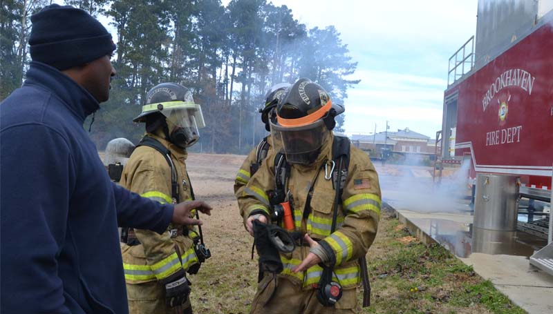 As smoke continues to billow from the trailer, Capt. Albert Brown Jr. (left in photo at right) talks with a firefighter about the exercise. Brown said the department members participating in the drill were Capt. Kelly Porter, Lt. Blake Wallace, Lt. Aaron Welch and firefighters Chris Davis, Fredrick Kees and Lance Lewis.
