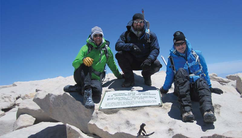 PHOTO SUBMITTED / Miranda (from left), Kirk and Saylor pose by the monument put there by the U.S. Department of the Interior, marking the apex of Mount Whitney in California at 14,505 feet.