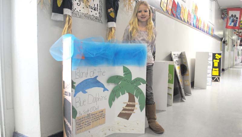 """THE DAILY LEADER / JUSTIN VICORY / Quinn Boerner stands next to her reading fair presentation, a creative depiction of """"Island of the Blue Dolphins,"""" a book by Scott O'Dell. Over 170 students participated in the fair at Brookhaven Elementary School."""