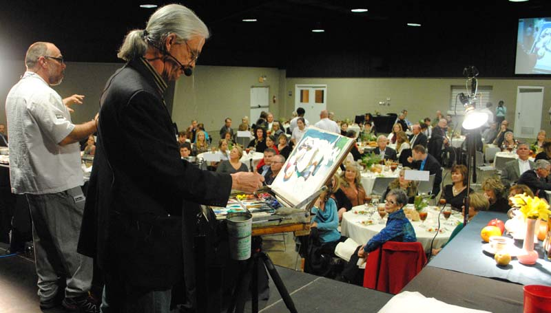THE DAILY LEADER / RHONDA DUNAWAY / Mississippi chef, author and food columnist Robert St. John (left) speaks to the audience at Thursday night's PaLate event as Mississippi watercolorist Wyatt Waters (right) paints a still life set up for the occasion.