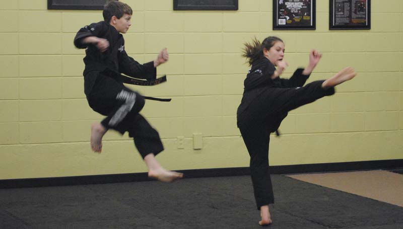 DAILY LEADER / RHONDA DUNAWAY / Payton Domanick and Trinity Stinson practice kicks during special black belt training.