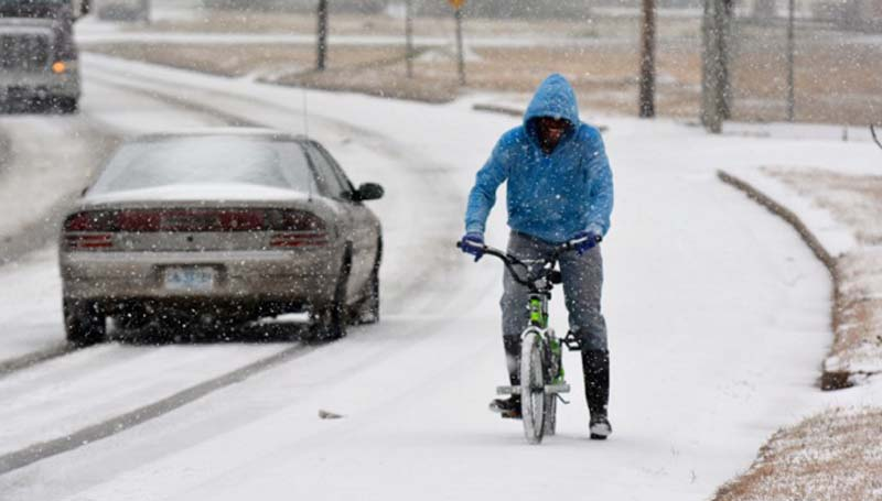 DAILY LEADER / SCOTT BOYD / Braon Nelson, 16, of Brookhaven, makes his way down Industrial Park Road on his bicycle Tuesday morning in the sleet and snow.