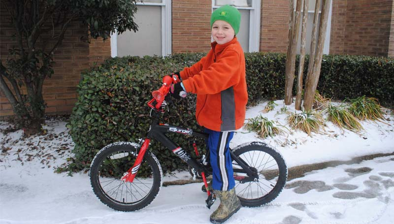 THE DAILY LEADER / JUSTIN VICORY / Colton Richardson finds a way to ride his bicycle despite layers of ice and snow coating the roads and sidewalks Wednesday.