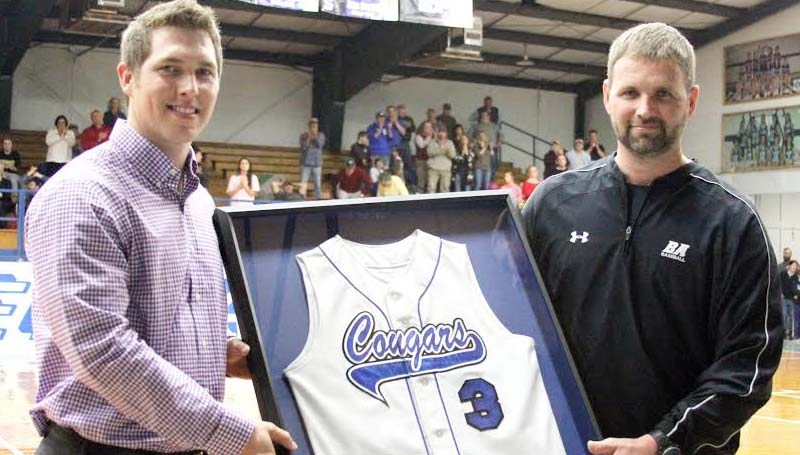 DAILY LEADER / SHERYLYN EVANS / Corey Dickerson (left) proudly holds his retired high school jersey along with BA head baseball Coach Casey Edwards during a special ceremony Friday night at John R. Gray Gymnasium.